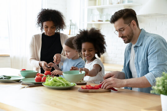 Happy diverse parents with adorable daughters preparing meal together, African American mother and Caucasian father with two little kids cooking salad, multiracial family enjoying leisure time