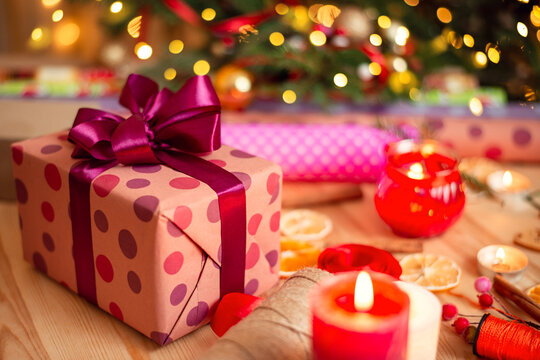 Close-up picture of gift with big purple bow with some candles and other christmas decorations on the table. Decorated christmas tree on the background