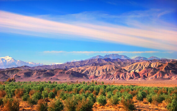 Amazing nature scenery - bizzare colorful rocks - mountain range at the background of blue sky at sunset time and green orange trees. View from Tehran - Isfahan road, Iran, Middle East, Western Asia.
