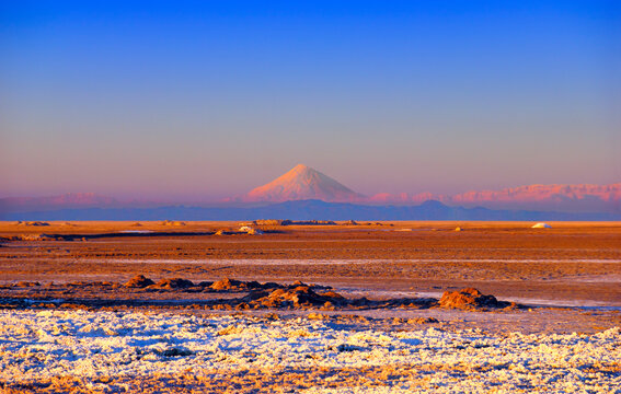 Colorful sand, white salt, blue sky and distant mountain range with Damavand mount (Demavend volcano) - the highest peak of Middle East, view from Maranjab desert, Aran va Bidgol, Iran