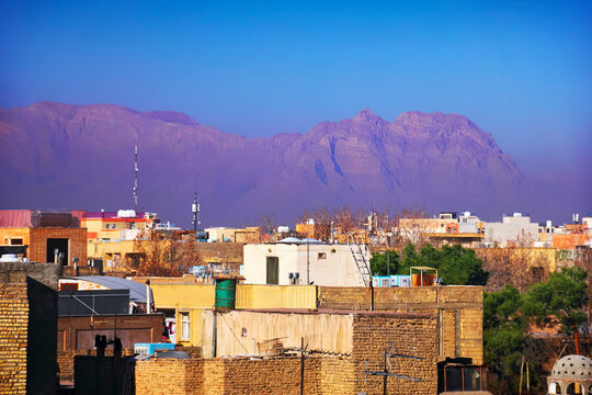 Beautiful city scape, old and modern houses at the background of purple barren mountain range, haze or smog and blue sky at evening, view from the roof, Isfahan (Esfahan), Iran (Persia), Middle East