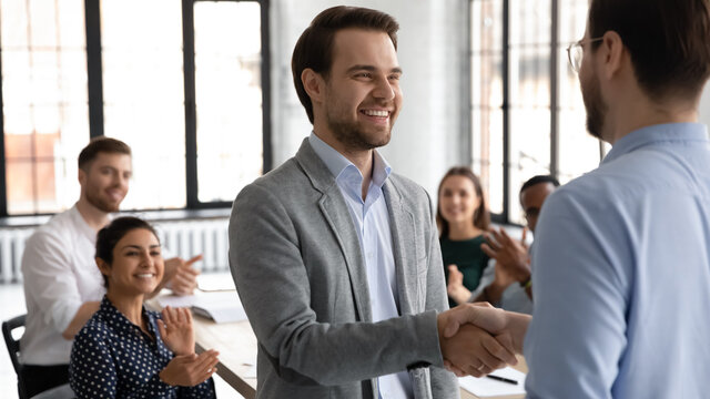 Happy motivated millennial man intern is being hired on regular job employed to international company, loyal young male manager handshaking with leader employer on formal meeting with corporate team