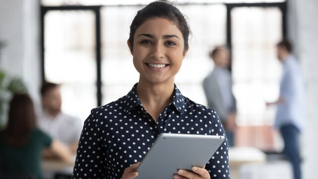 Glad to help you. Portrait of smiling confident indian female insurance broker bank manager hr assistant standing in open space office holding digital tablet looking at camera ready to assist client