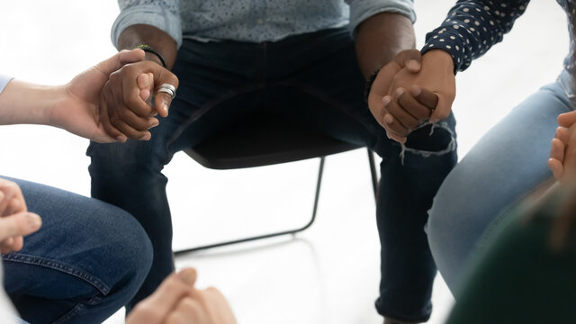 Completing the circle. Close up of multiethnic people sitting on chairs around holding neighbors partners palms uniting hands in symbolic loop feeling support struggle with addiction to alcohol drugs