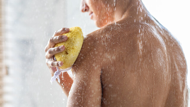 Young man washing his body with sponge