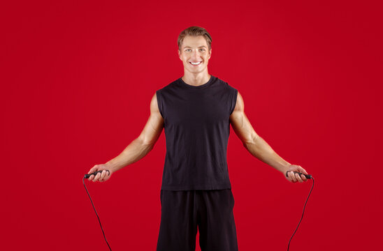 Cardio workout concept. Young fit sportsman jumping on skipping rope over red studio background