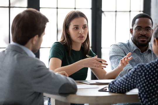 Two diverse multiethnic groups of business partners sitting at negotiation table, concentrated millennial female employee explaining plan project details to interested teammates on meeting in office