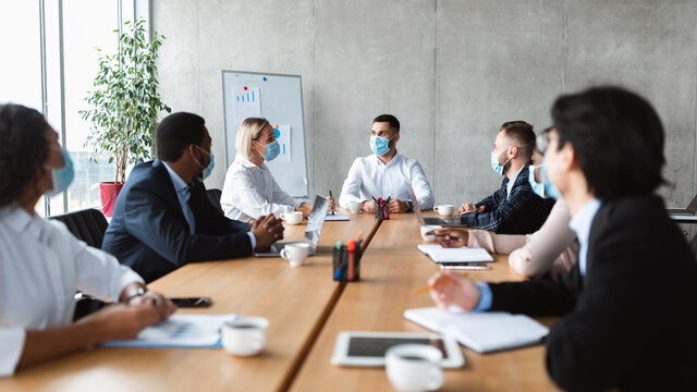 People In Face Masks Sitting During Corporate Meeting In Office