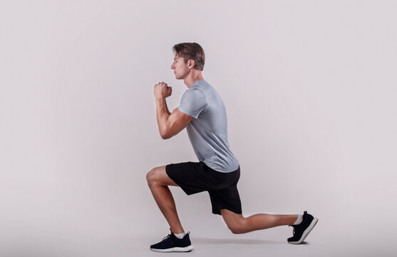Side view of young fit guy in sportswear doing lunge on light studio background