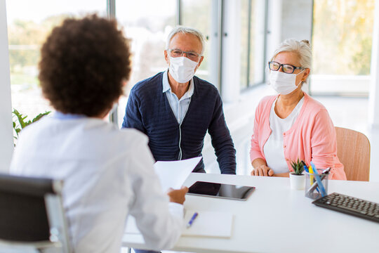 Senior couple with protective facial masks receive news from black female doctor