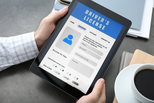 Man holding tablet with driver's license application form at grey table, closeup