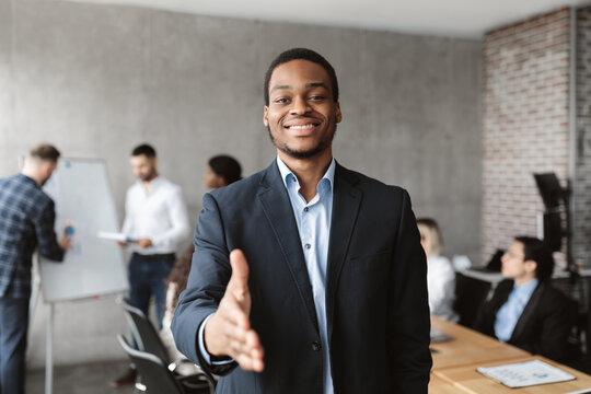 Black Businessman HR Stretching Hand For Handshake In Modern Office