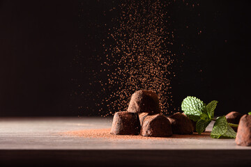 Chocolate truffles with mint leaves on table falling cocoa powder