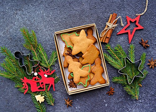 Homemade Christmas cookies or gingerbread cookies of various shapes in a cardboard box on a dark concrete background. Christmas cookies.