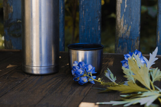 Thermos with tea and a purple flower on the background of nature and a fence. Stop in the journey. Wood texture