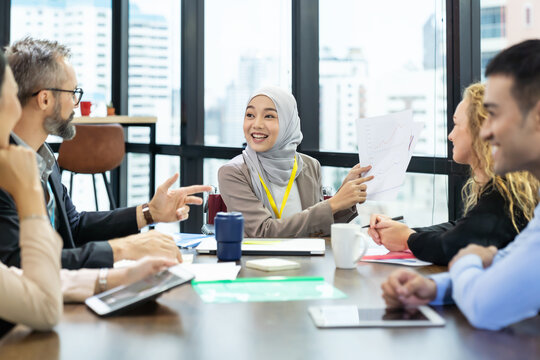 Asian Muslim business woman in hijab headscarf sitting on wheelchair presenting of her work to corporate colleagues in meeting in the modern office. diverse corporate colleagues and multicultural