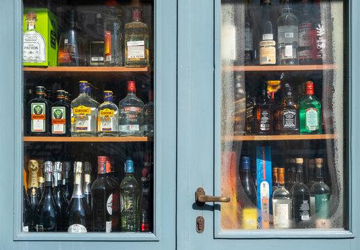 Alcohol spirits bottles display, Store shelves behind a blue glass door. Athens, Greece.