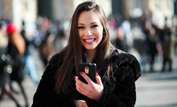 Beautiful young tourist girl in Milan using a smartphone