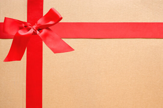 Wide red ribbon with bow on cardboard gift box. Top view, copy space