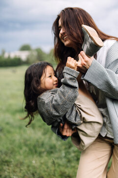 Mom and daughter have fun together. Weekend in nature near the forest in the grass