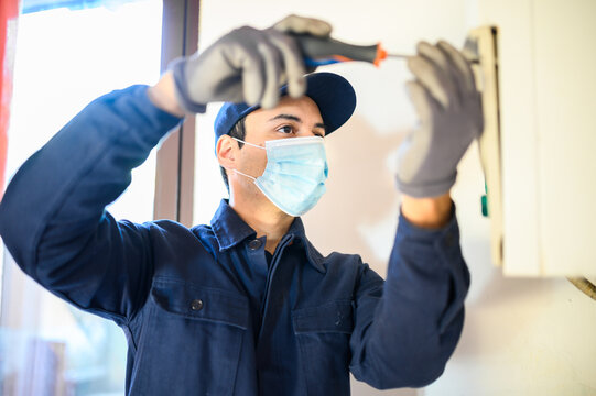 Smiling technician repairing an hot-water heater wearing a mask due to coronavirus pandemic