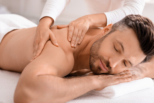 Closeup of handsome man having full body massage at spa