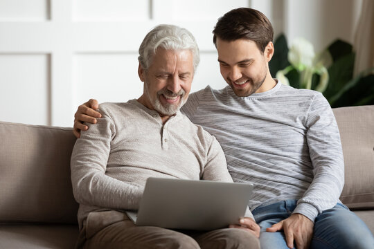 Happy senior father with adult son using laptop at home together, sitting on cozy couch, hugging, smiling mature grandfather with grandson looking at computer screen, young man helping to senior dad