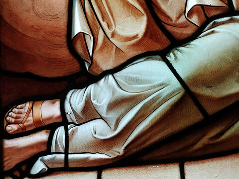 Scene of a body lying on the floor dressed in a robe and sandals. Stained glass window detail.