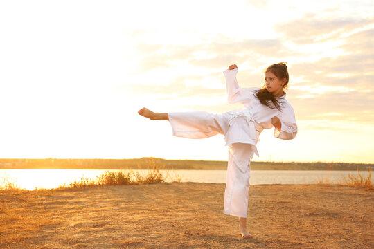 Cute little girl in kimono practicing karate near river at sunset