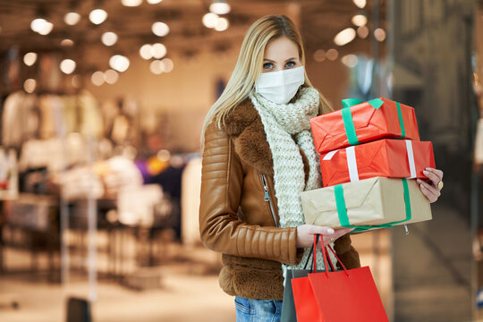 Portrait of adult woman shopping in mall wearing a mask, coronavirus concept