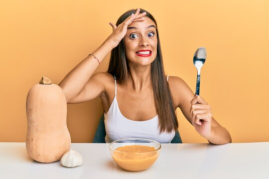 Young hispanic woman eating pumpkin soup with spoon stressed and frustrated with hand on head, surprised and angry face
