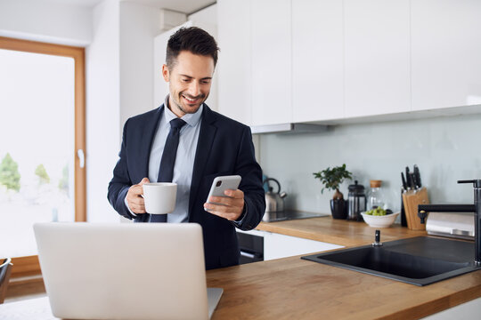 Businessman using mobile phone standing in kitchen