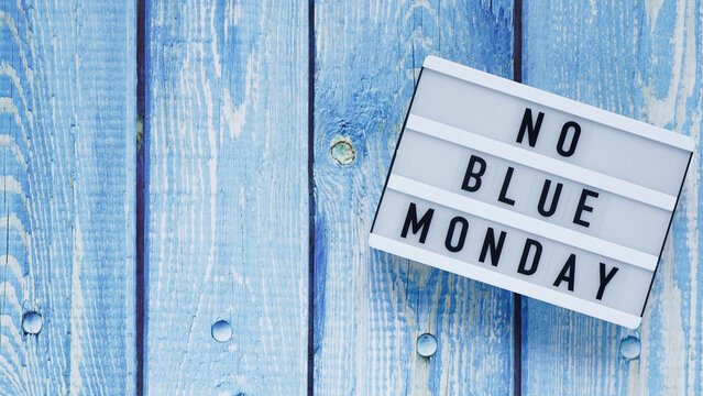 Blue monday day banner concept. White board with text no blue monday on blue wooden background, top view, flat lay. Copy space.