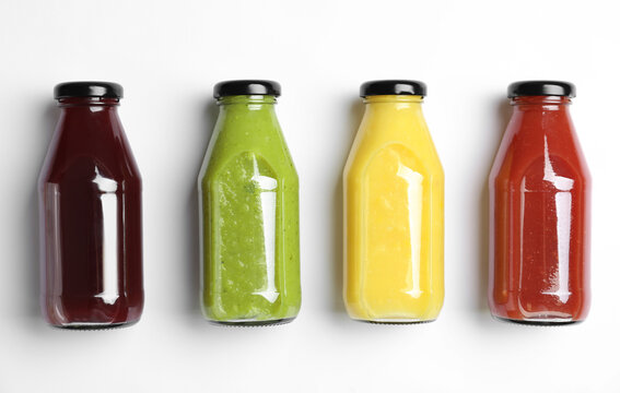 Bottles with delicious colorful juices on white background, flat lay