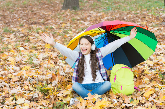 happy kid wear headphones under colorful umbrella. girl listen music. positive child relax in autumn forest. fall leaves in park. back to school. online education. seasonal weather