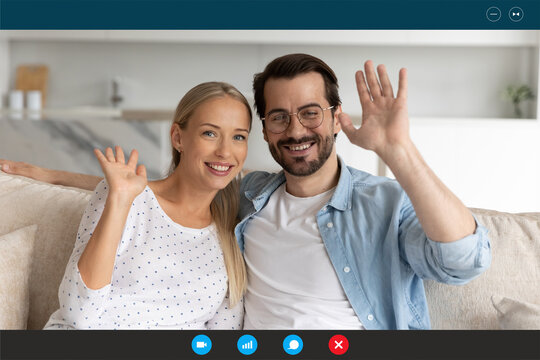 Happy young european family couple resting on couch, waving hand in hello gesture, greeting friends at online video call distant meeting, enjoying pleasant conversation at home, app screen view.