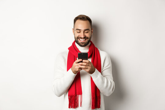 Happy man smiling while reading message on mobile phone, standing in winter sweater and red scarf against white background