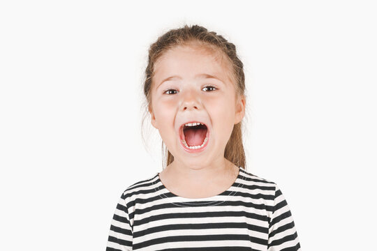 Loudly yelling or singing girl. Girl looking at camera with wide open mouth. Posing little girl wearing striped shirt. Isolated background. Announcement, attention, checkup at a dentist concept.