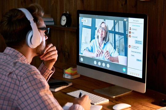 Male student wearing headphones taking online course training, watching webinar, remote seminar university class, virtual learning with social distance web teacher, tutor or coach on computer screen.