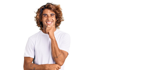 Young hispanic man wearing casual white tshirt looking confident at the camera smiling with crossed...
