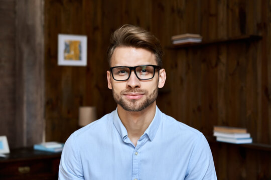 Confident young adult businessman wearing glasses looking at camera in office, charming millennial professional, male small owner, coach, leader, entrepreneur headshot face front close up portrait.