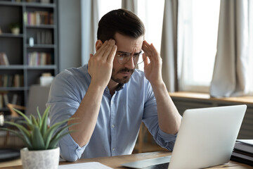 Businessman sit in front of laptop touches temples feels stressed, troubles in business. Male...