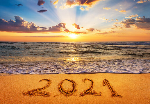 Happy New Year 2021 is coming concept. Number 2021 written on seashore sand at sunrise.