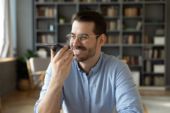 Businessman sit in office holds smartphone leave voice message, solve business issues remotely, use loudspeaker virtual assistant search information on internet. Easy comfort modern tech usage concept