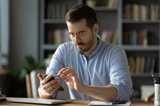 Serious businessman wearing spectacles using mobile phone sit at desk in cozy office. Manager solve issues with client remotely by modern wireless device, surfing web, learn new business app concept