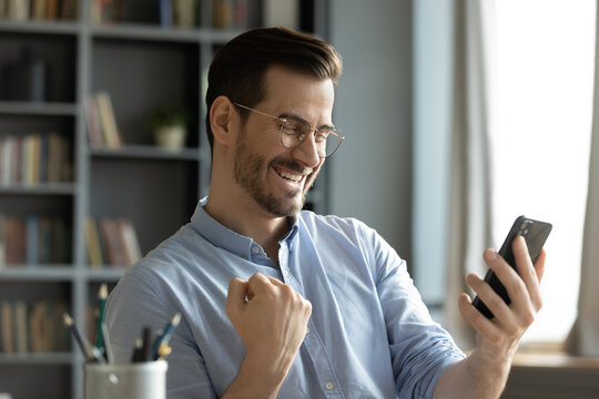 Happy young man sitting at home office room holding smartphone read message feel amazed by great on-line news. Salary growth sms from bank, gambler celebrate auction game victory, monetary win concept