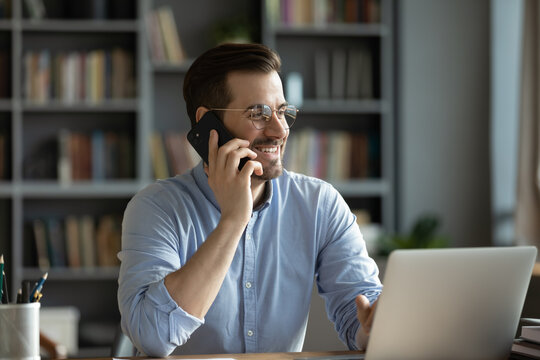 Smiling good-looking businessman in glasses sit at workplace desk in modern office room using wireless device holding smartphone talking to client, solve issues remotely. Business conversation concept