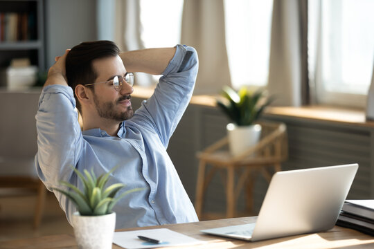 Handsome young businessman resting at workplace lean on comfort chair closed eyes enjoy fresh conditioned air. Satisfied employee finish work feels serene relaxing in modern office, no stress concept