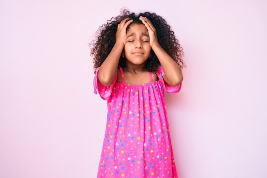 African american child with curly hair wearing casual dress suffering from headache desperate and stressed because pain and migraine. hands on head.