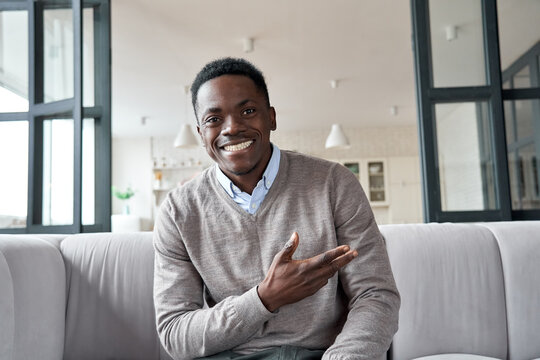 Happy african young man online coach, distance job applicant looking at camera or web cam video conference calling in virtual webcam chat interview meeting sitting on couch at home. Headshot portrait.